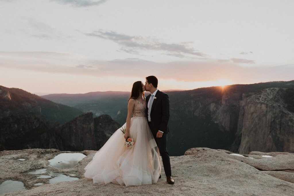Newlyweds share a kiss at sunset on top of California mountain.