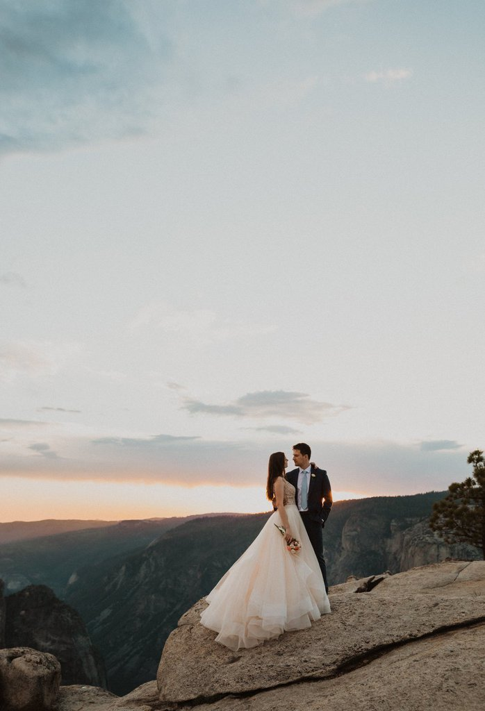 bride and groom standing at the edge of the mountain in California.