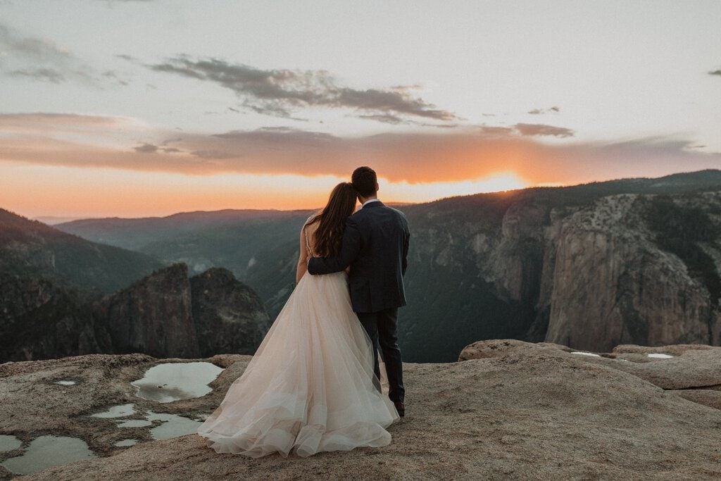 bride and groom watch the sun set at Yosemite national park.