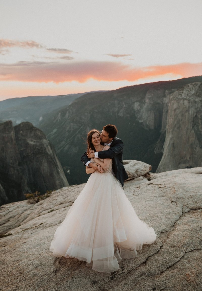 bride and groom embrace at sunset.