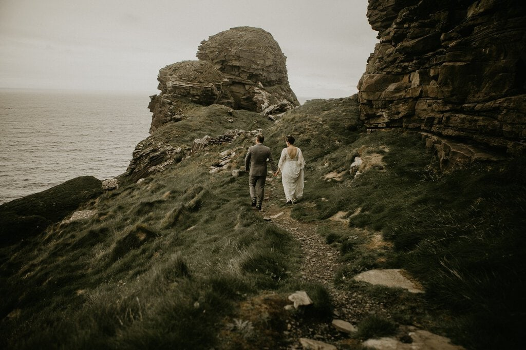 bride and groom hike up cliffs of moher.