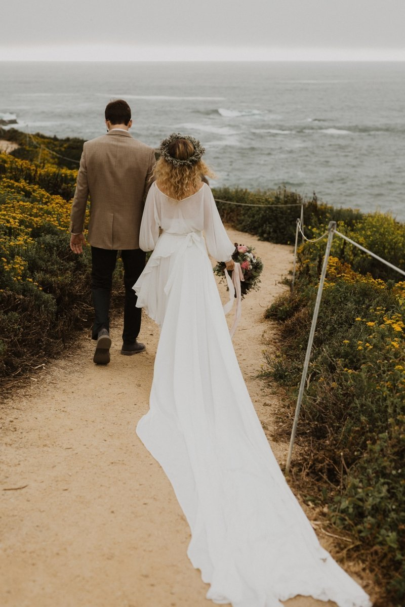 Bride and groom walking down the coast of California state park.