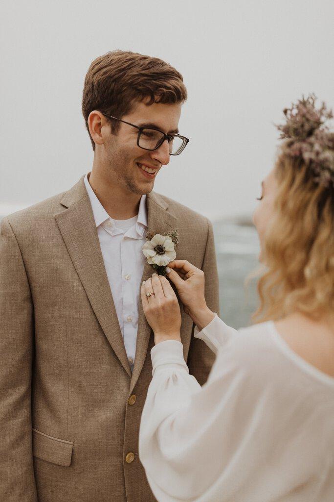 Bride adjust boutonniere on groom.
