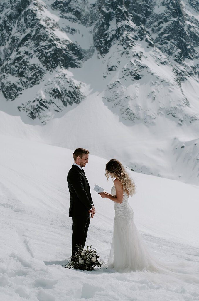 bride and groom exchange vows in snow.