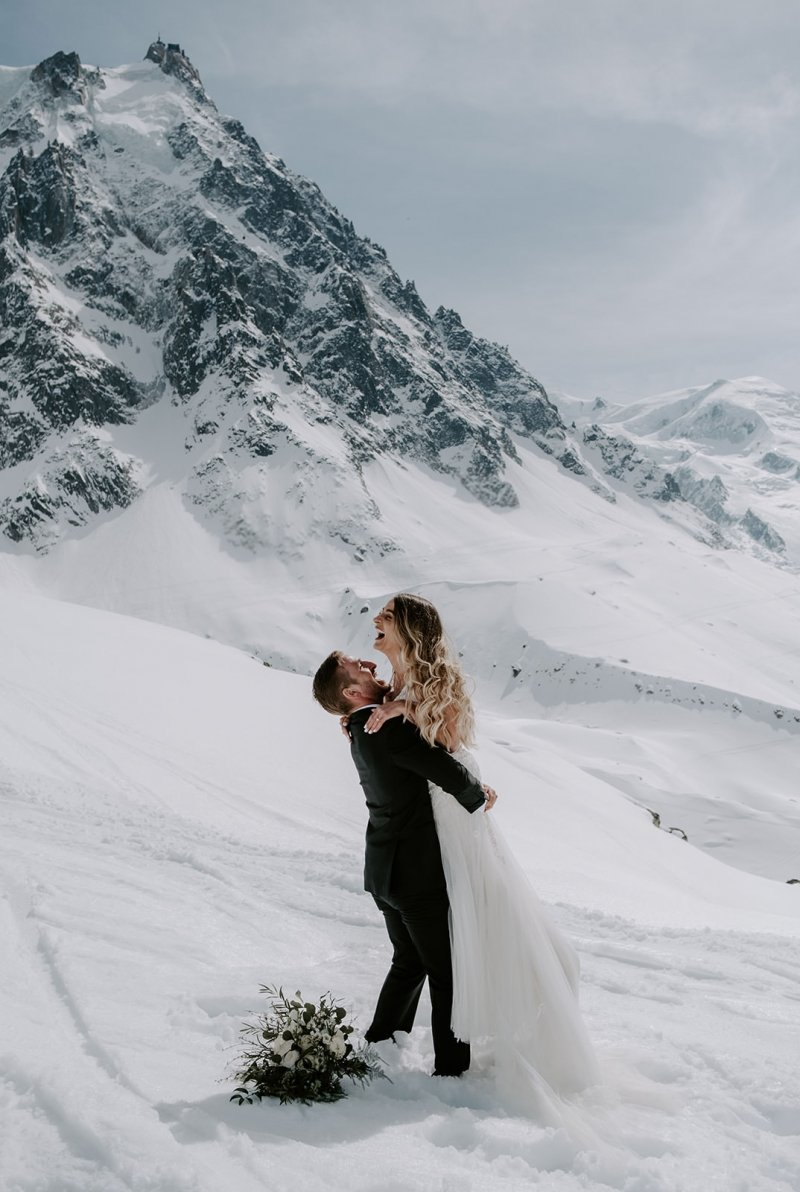 Bride and groom with snowy mountain.