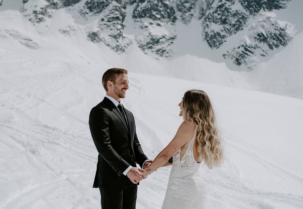 Bride and groom hold hands in snowy mountain.
