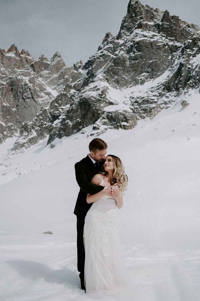 bride and groom hug in front of snowy mountain.