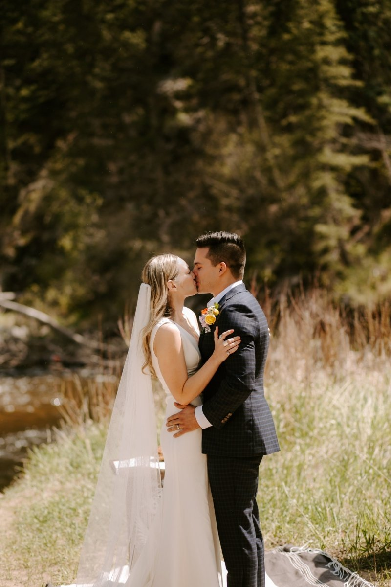 Bride and groom share their first kiss at intimate wedding in Colorado