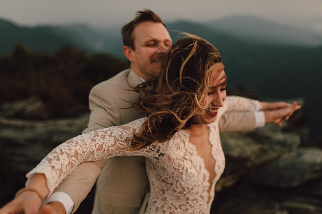 couple celebrate together on top of north Carolina mountain.