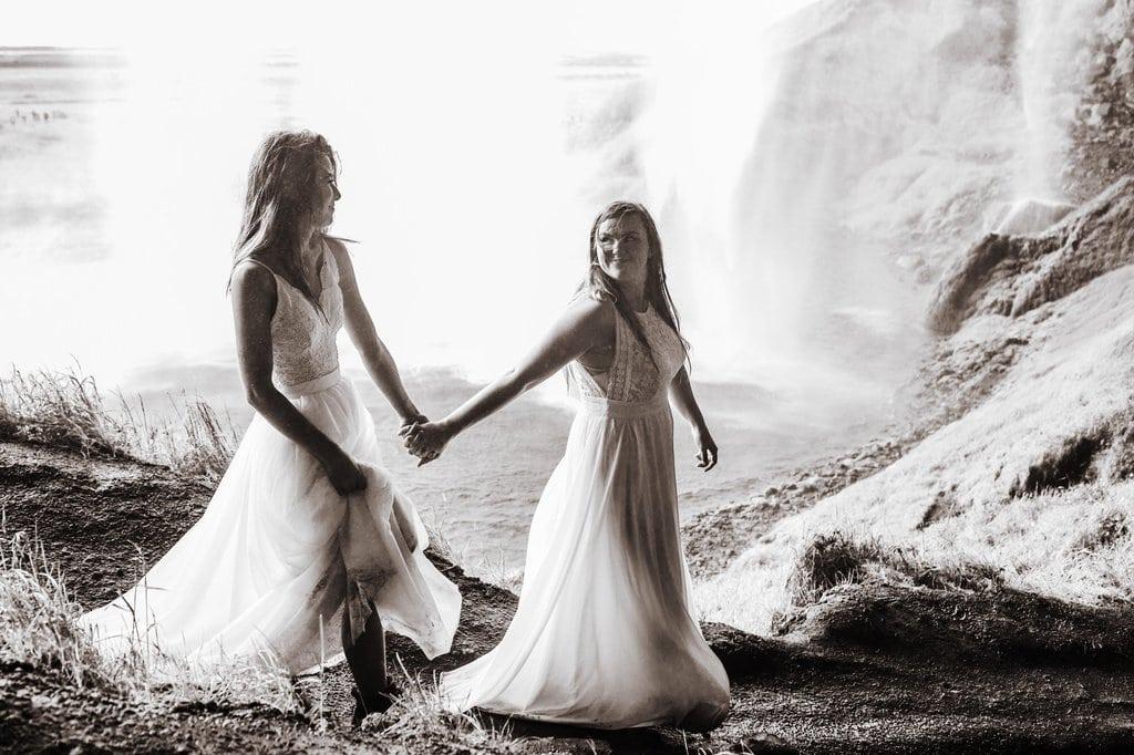brides hiking behind a waterfall.