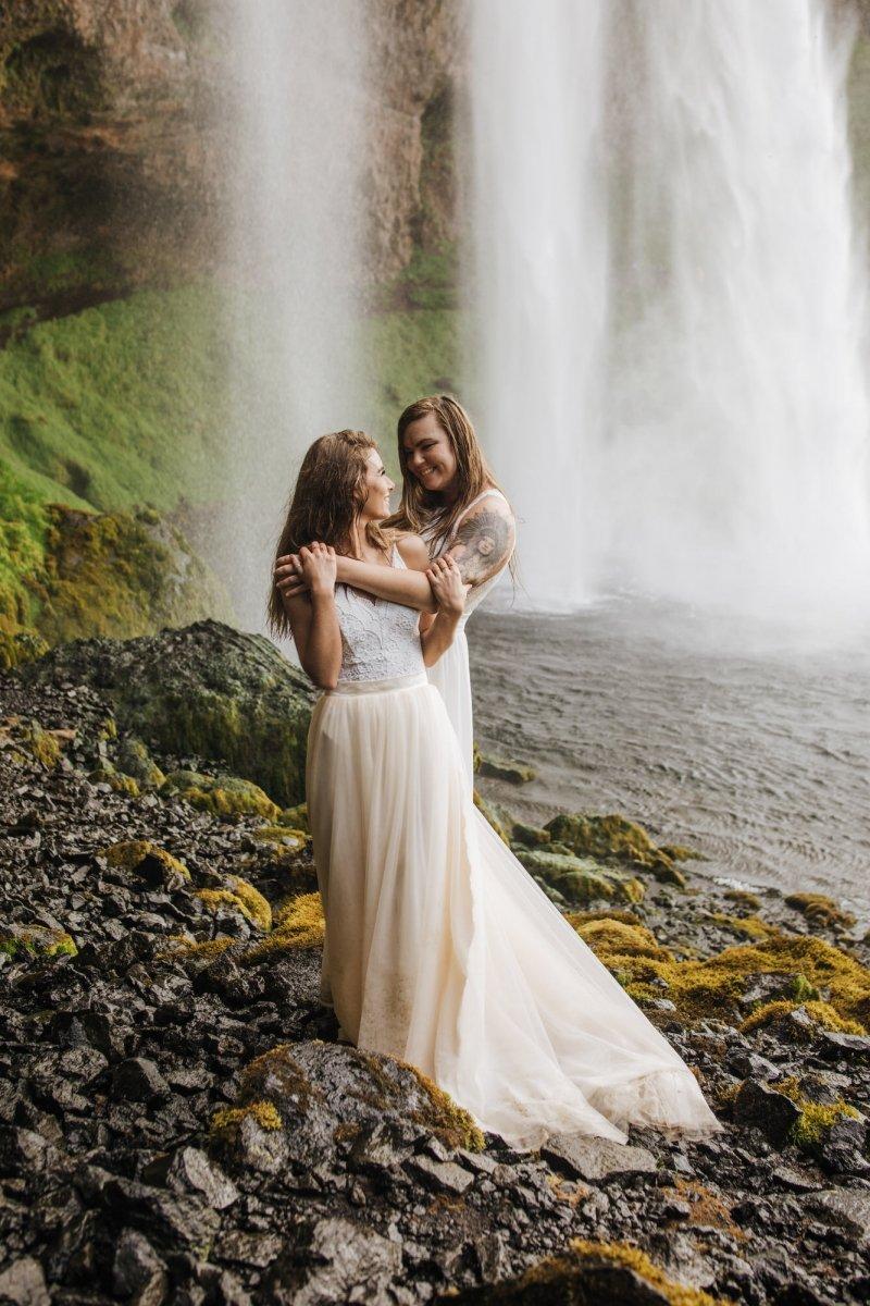 Brides hug during adventure elopement.