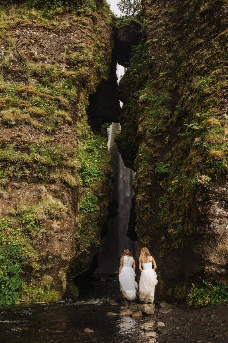 Brides hiking at Seljalandsfoss Cave in Iceland.