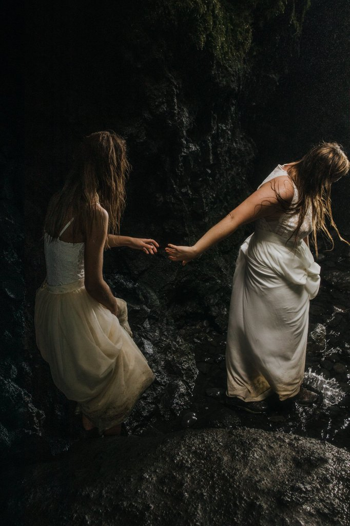 Brides hiking in Seljalandsfoss Cave.