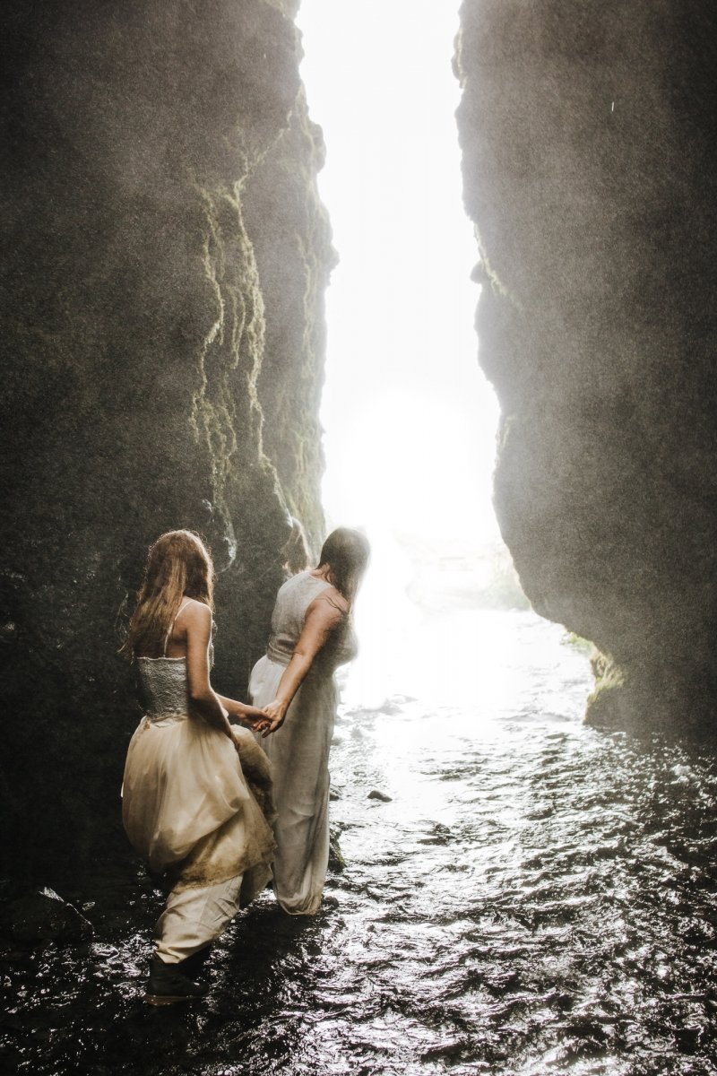 Brides hiking in Iceland cave.