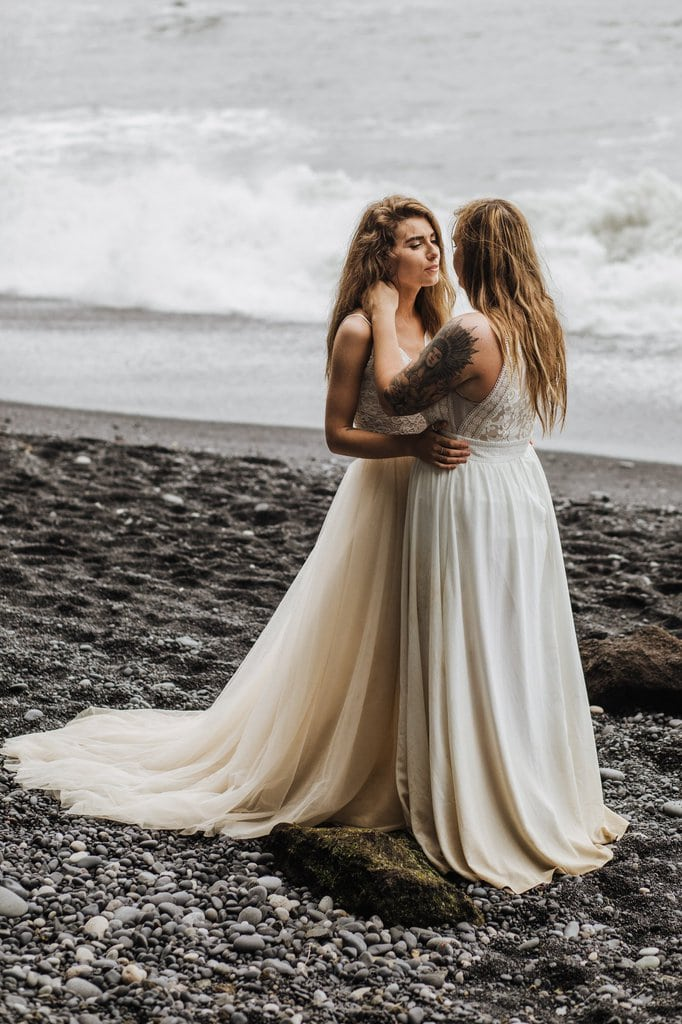 Brides hugging by the black sand beach.