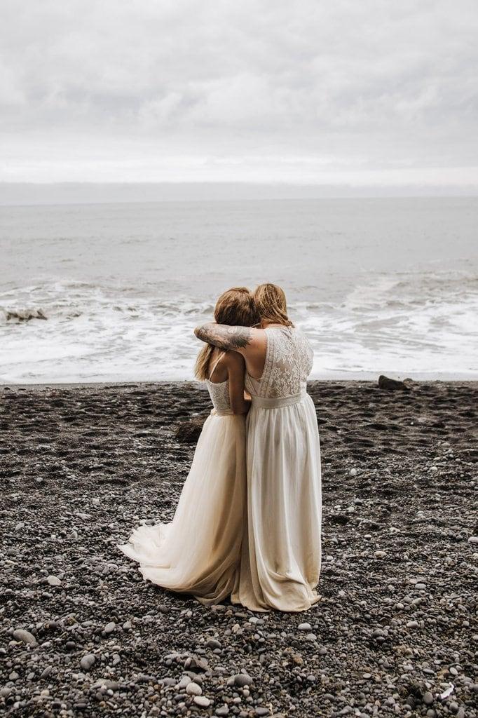 Couple hugging while looking out at Vik. Reynishfjara.