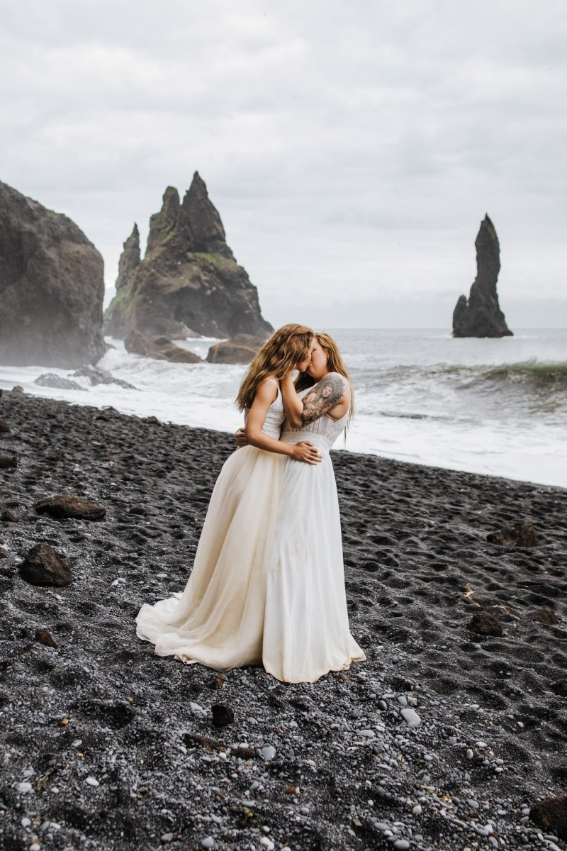 Brides kissing at the beach in Iceland.