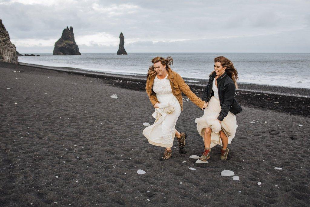 Brides running in Iceland's black sand beach.