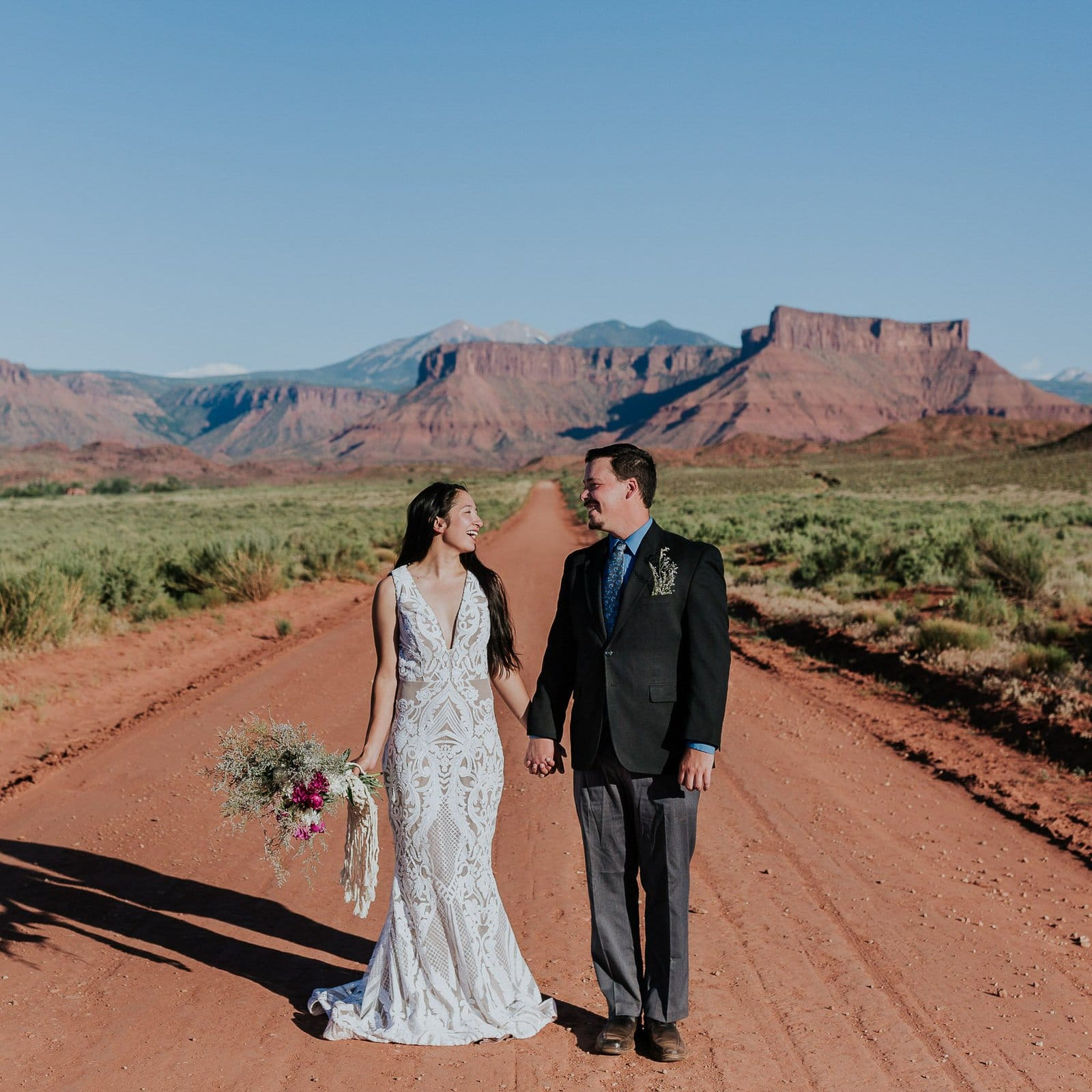 Bride and groom walk down the road of Moab, Utah.
