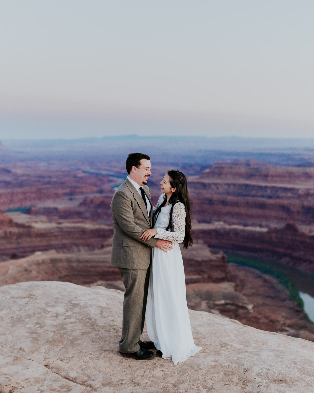 Bride and groom embrace on mountain in Moab.