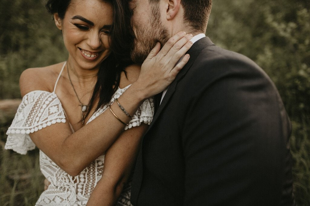Bride laughing as groom whispers in her ear.