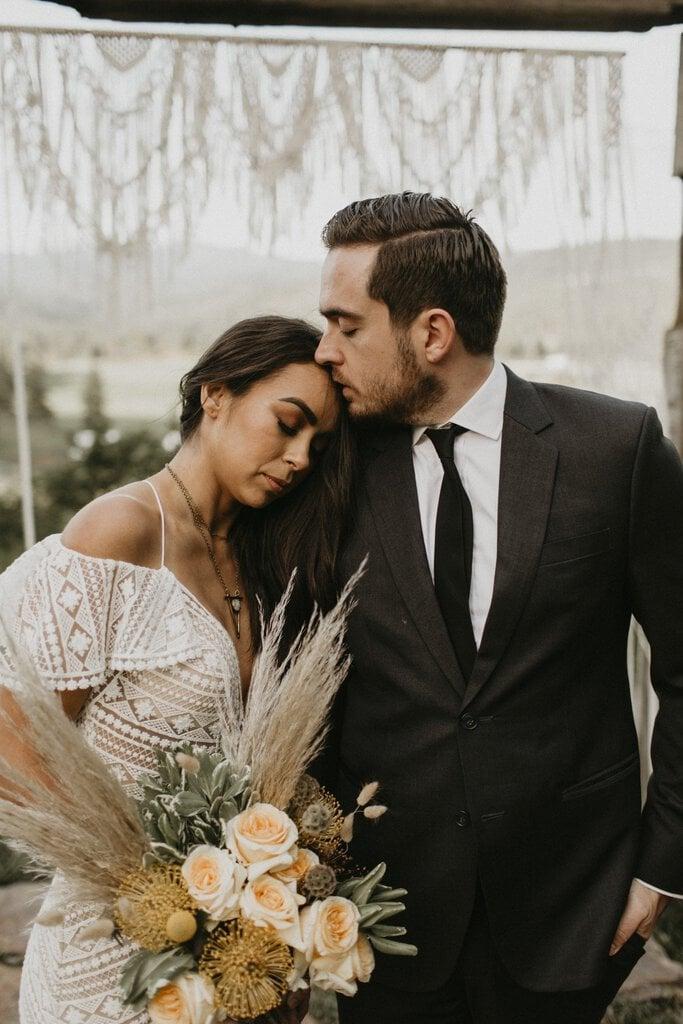 Groom kisses bride on forehead.