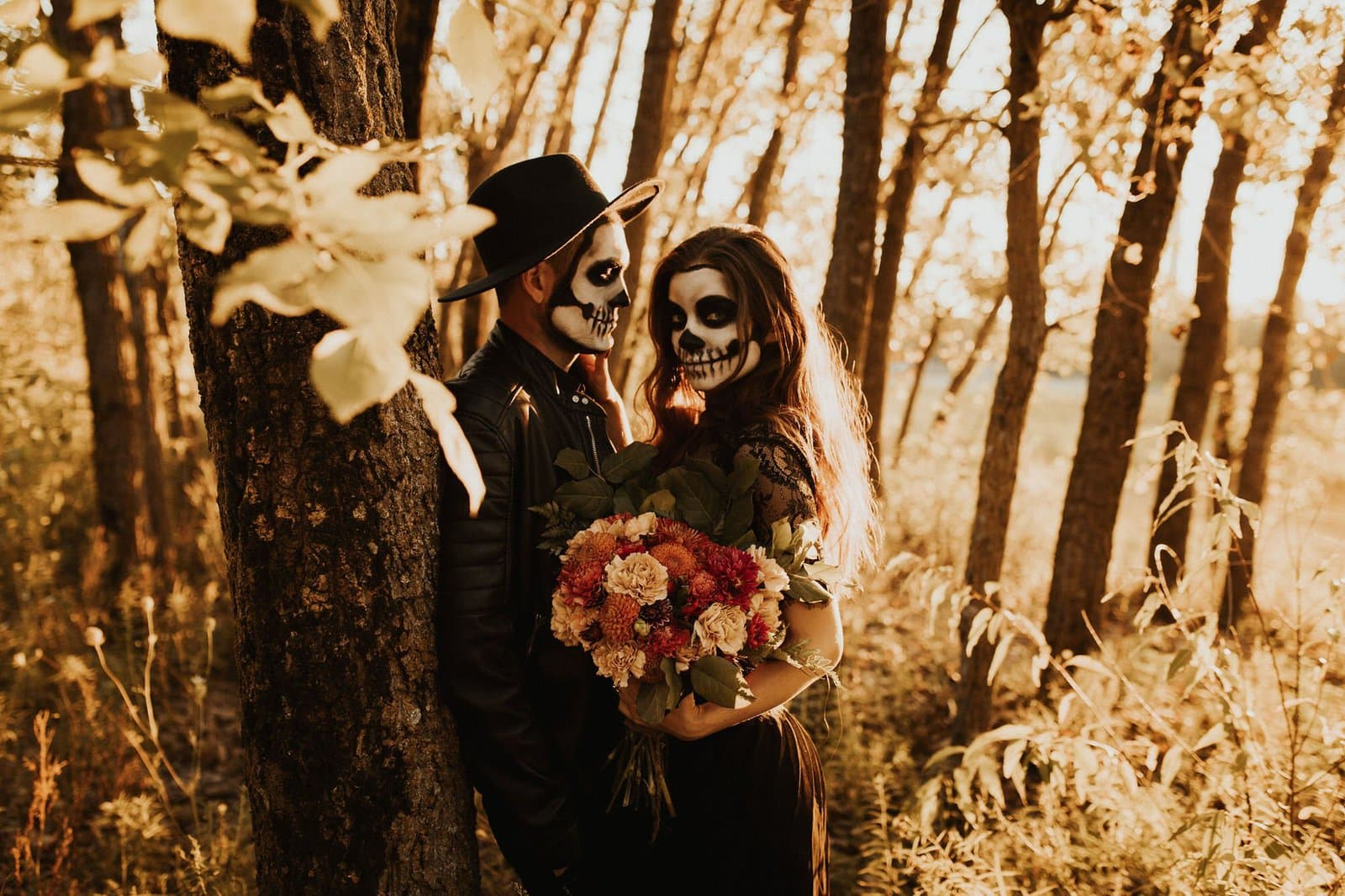 couple in woods embracing in skeleton makeup.