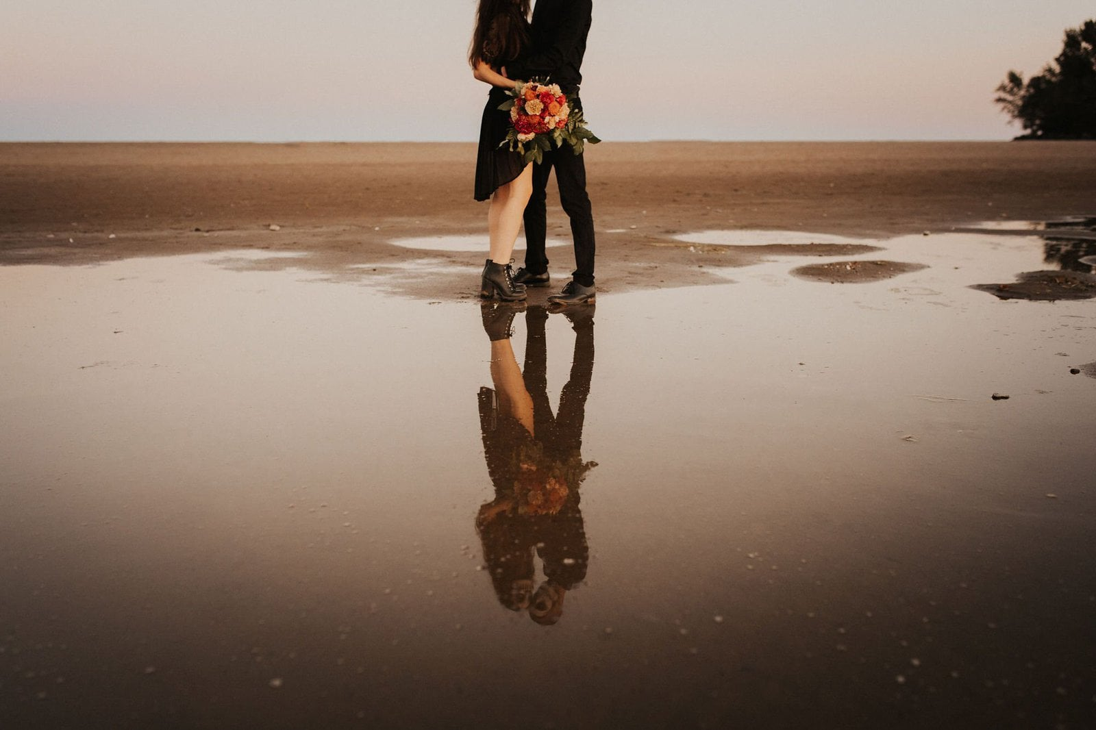reflection shot of couple on beach.