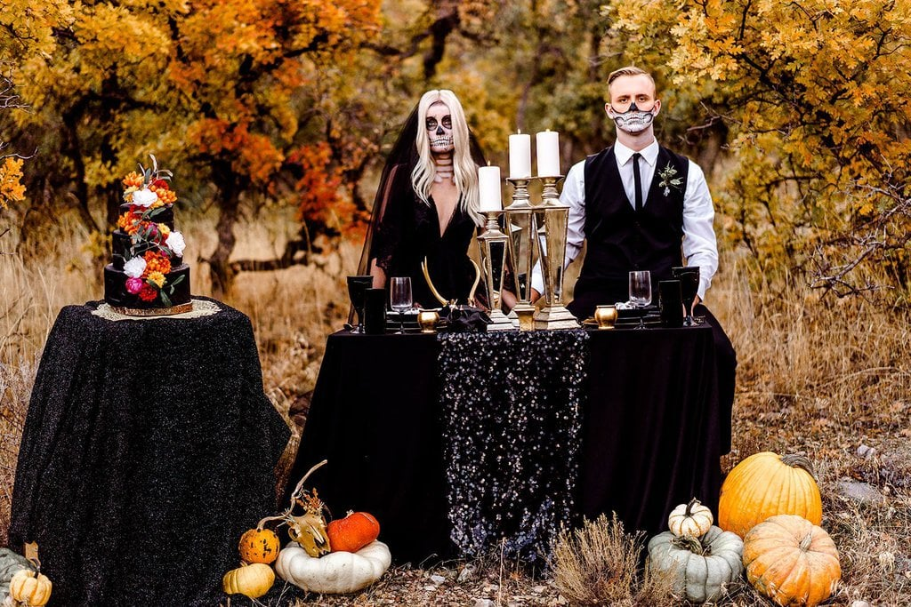 Bride and groom sitting at table for Halloween wedding.