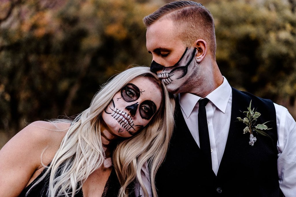 Groom kisses bride with skull paint.