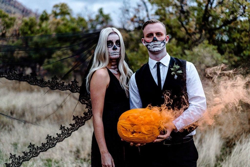 Couple holding pumpkin for Halloween elopement.