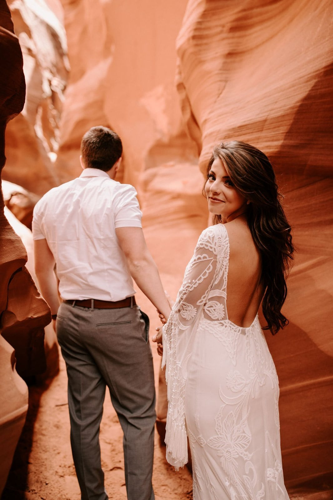 bride and groom walking in Antelope Canyon.