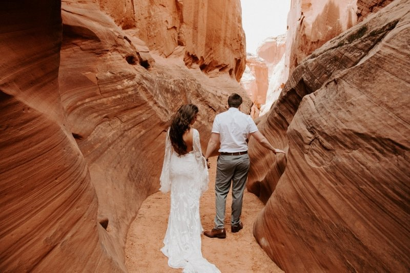 Bride and groom walk in antelope canyon.