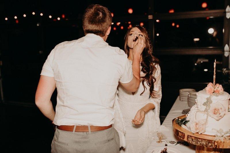 bride and groom eat their wedding cake.