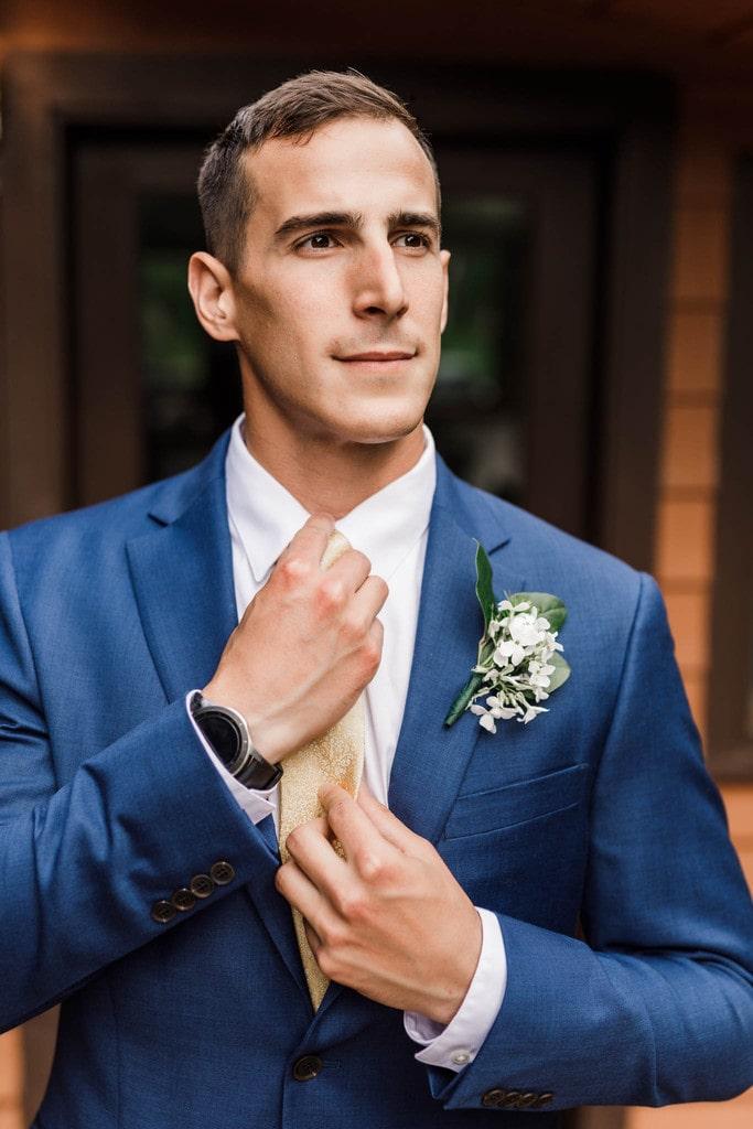 Groom portrait adjusting his tie