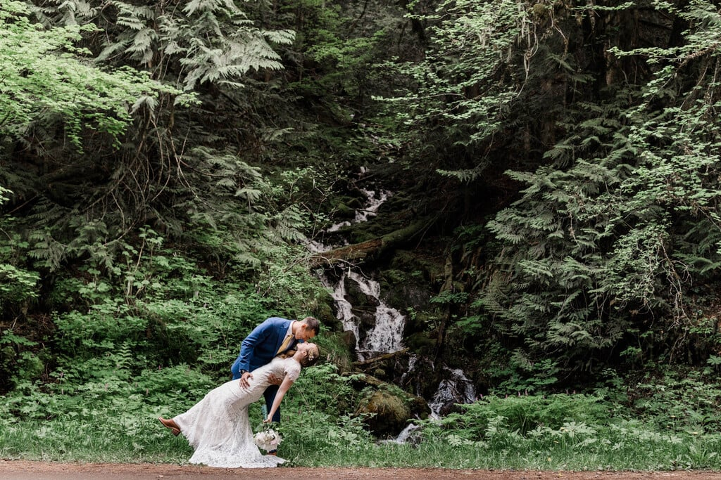 Groom dips bride in the mountains.