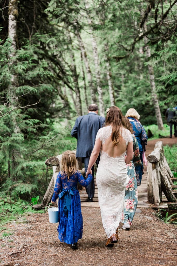 Bride and flower girl walking in the forest.