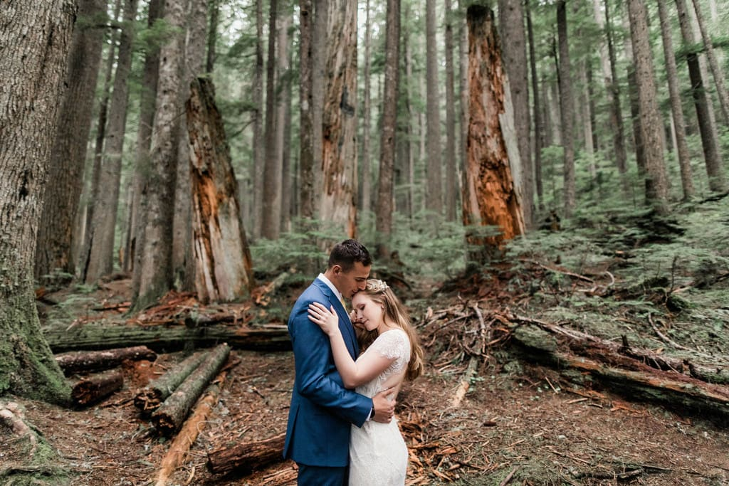 bride and groom hug in the woods of Mount Rainier national park.