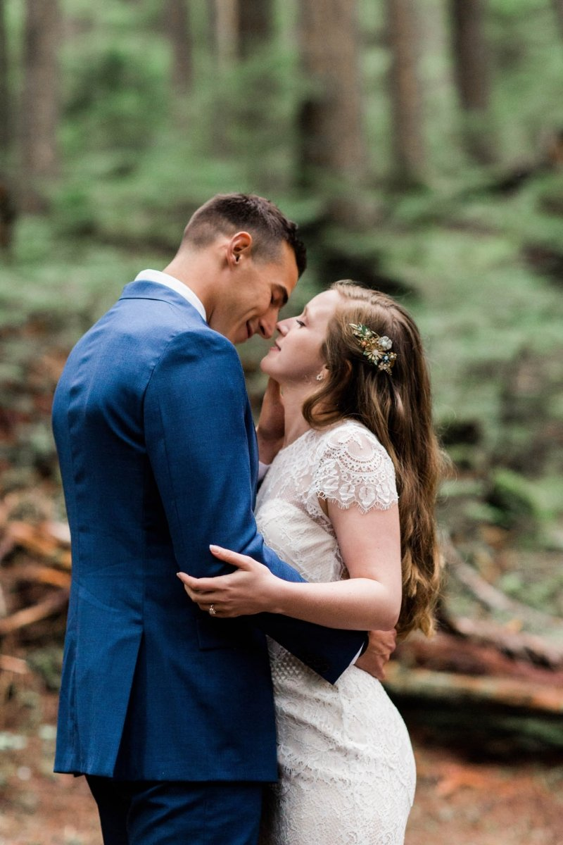 bride and groom share a kiss in the woods of Washington.