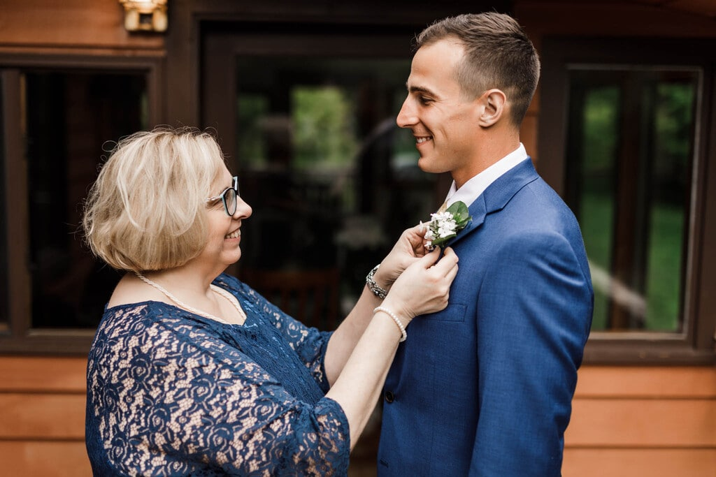 groom's mom adjusting his boutonnière..