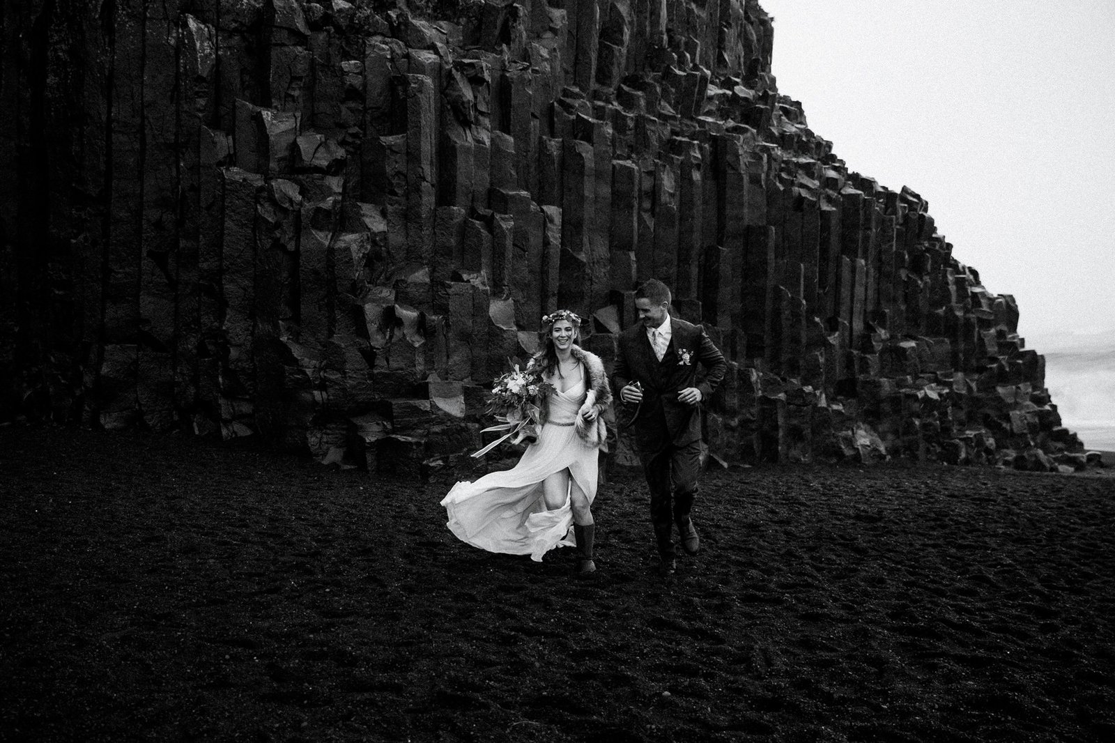Bride and groom running through Reynisfjara beach.