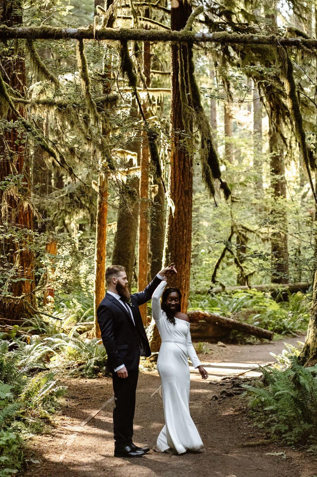Husband and wife dance in the forest of Olympic National Park.