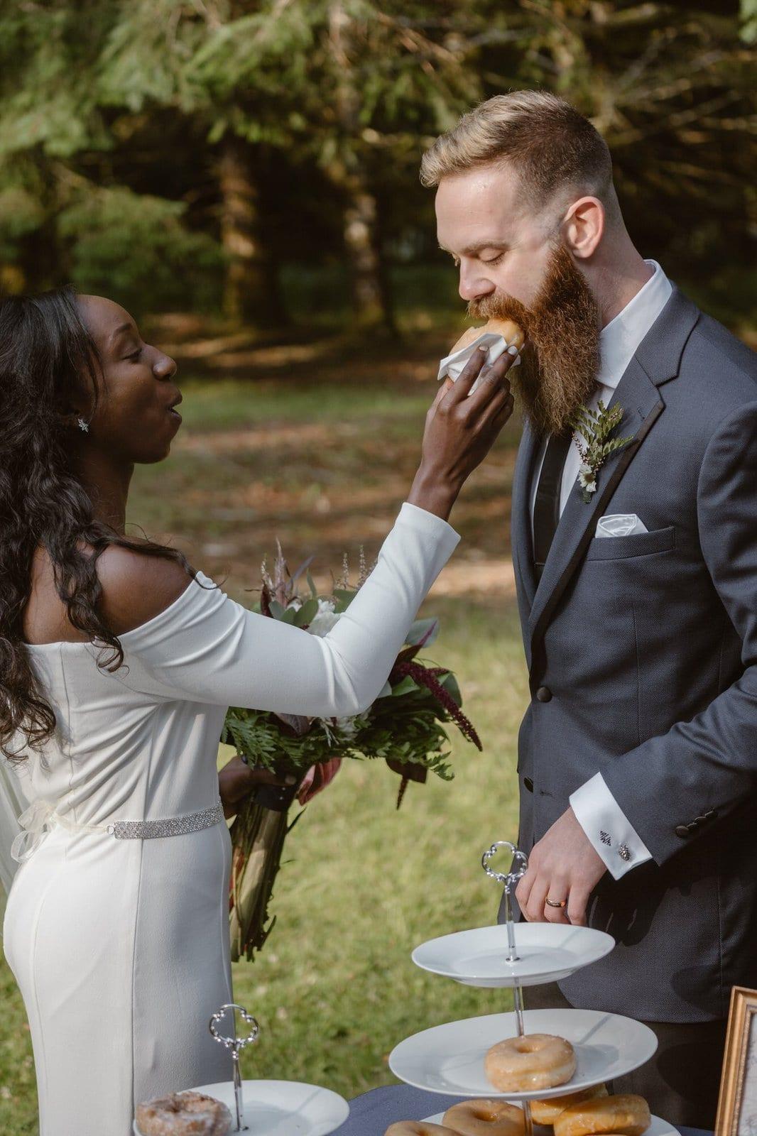 Bride feeds groom donuts at wedding.