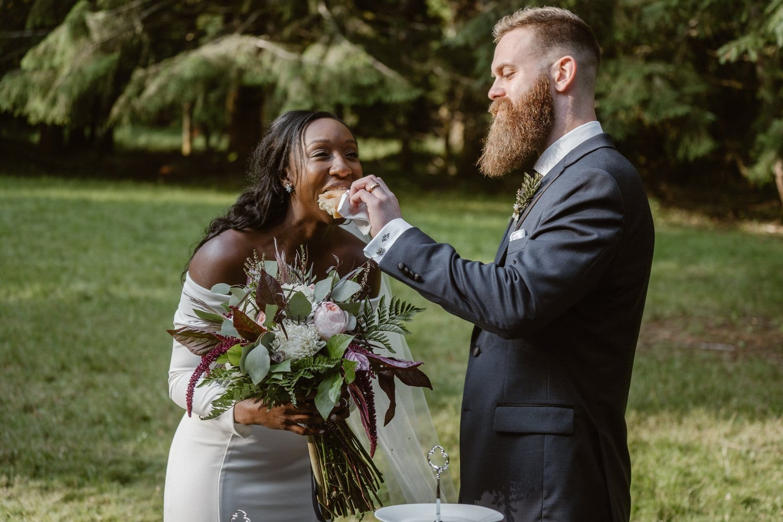 groom feeds bride donuts during intimate wedding.