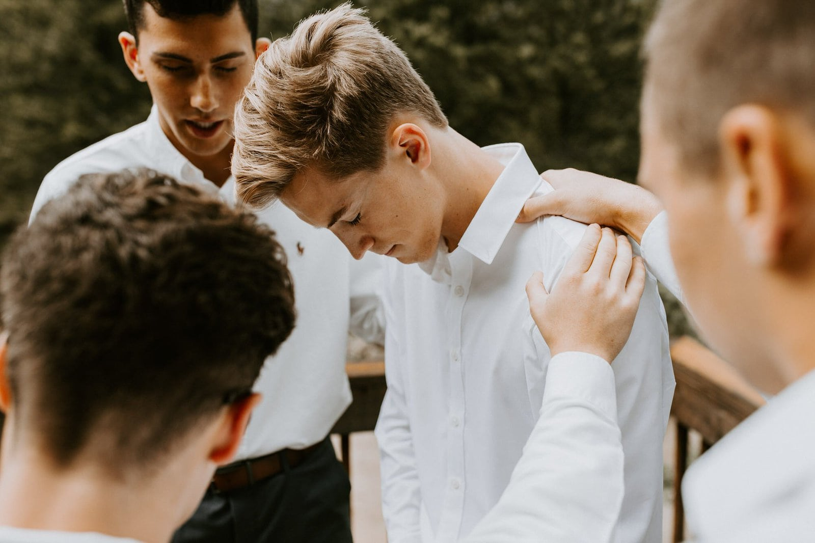 Groomsmen pray around groom.