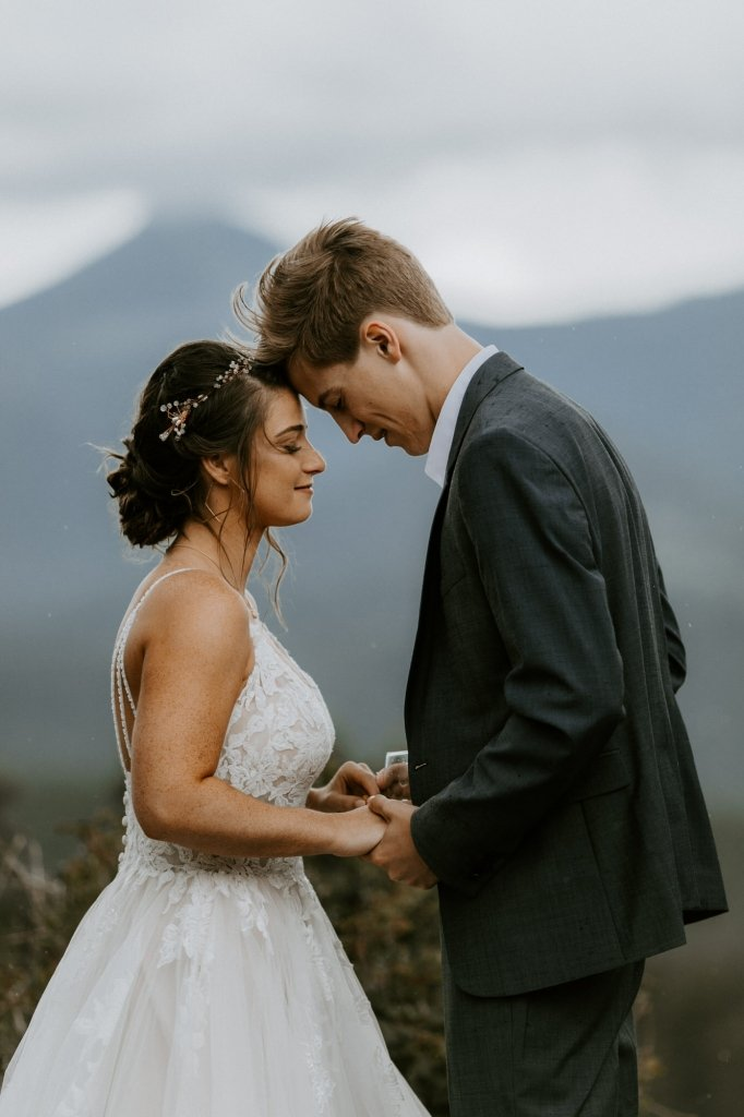 Bride and groom pray during rocky mountain wedding.