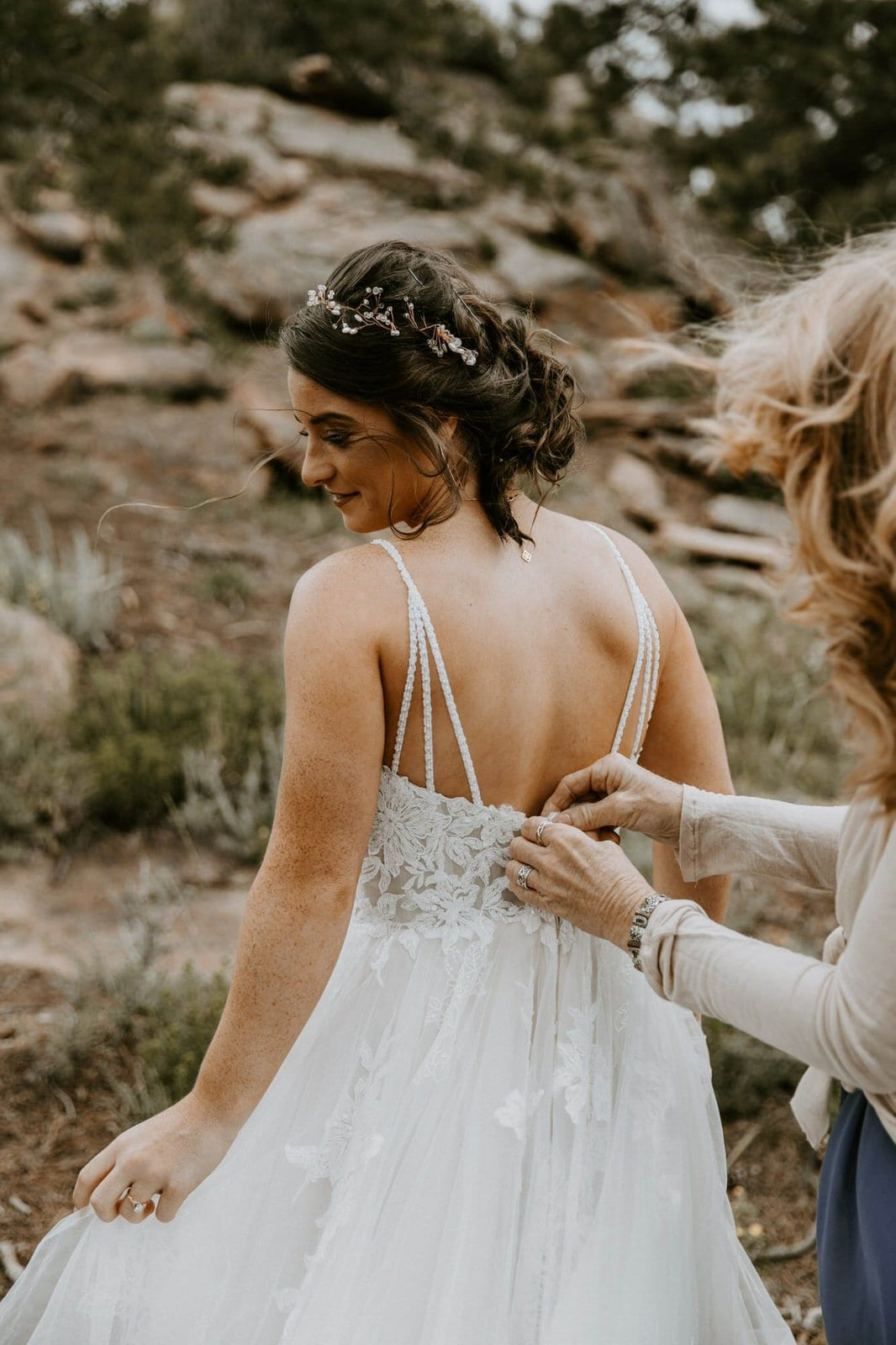 bride gets her dress buttoned up.