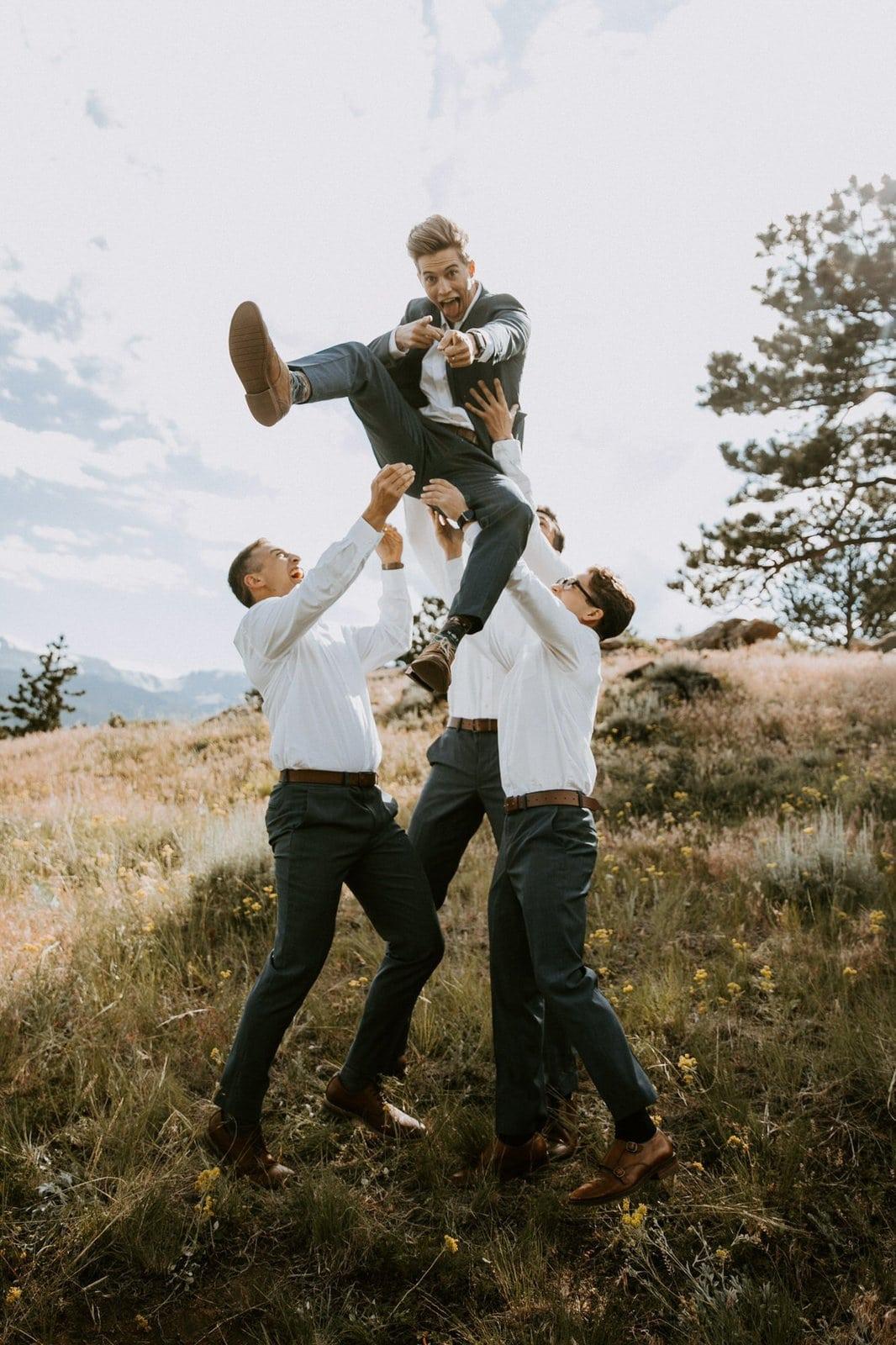 Groomsmen throw groom up in the air.