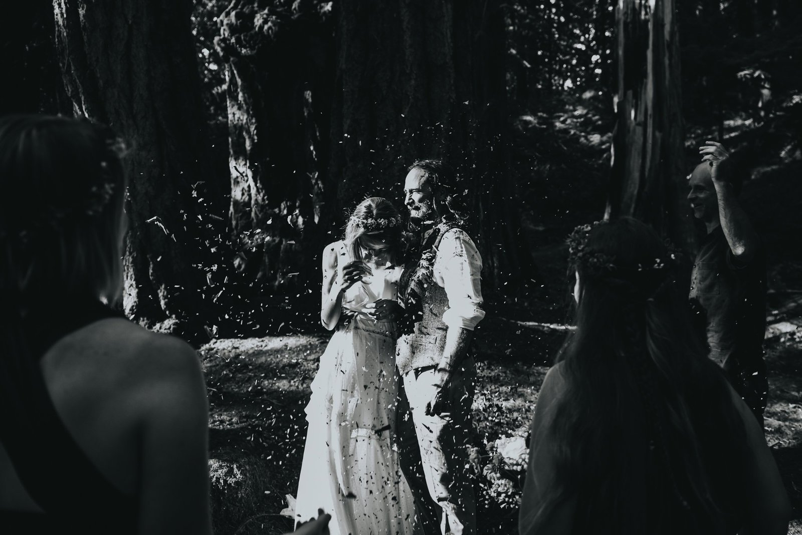 Bride and groom celebrate during intimate forest wedding.