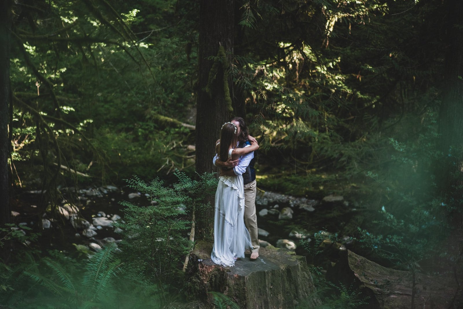 Bride and groom hug during intimate forest wedding.